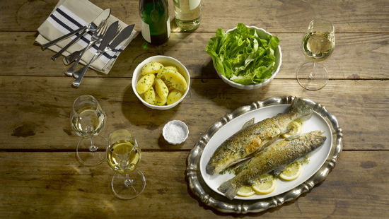 The picture shows trouts on a plate, standing on a wooden table