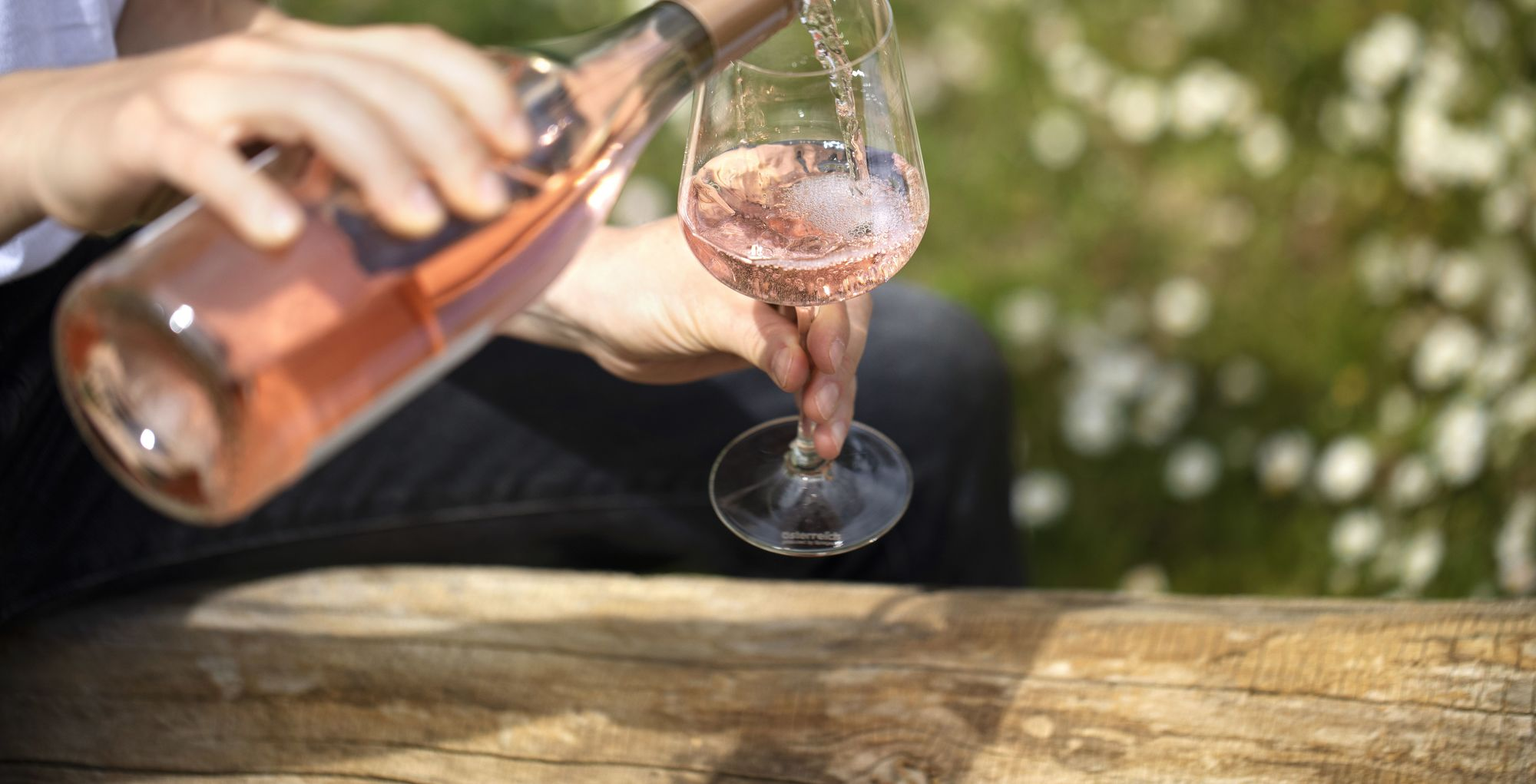 A woman is pouring Rosé from a bottle into a glass.