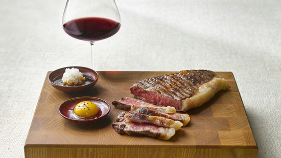 The picture shows wagyu beef and a glass of red wine.