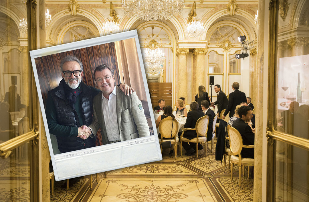 A picture shows Massimo Bottura with Willi Klinger in the foreground and a scene from the SALON Gala Dinner 2018 in the background, © AWMB