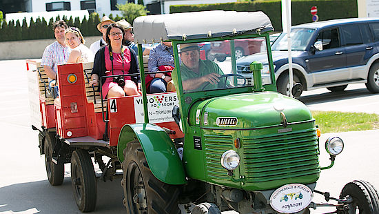 A picture shows guests of the Wine Summit on a tractor