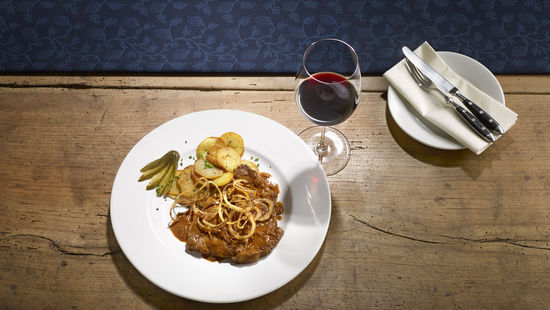 The picture shows the dish roast beef with onions and a glass of red wine.