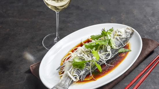 The picture shows steamed fish with a glass of white wine.