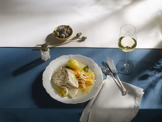 The picture shows carp with root vegetables on a plate and a glass of white wine.