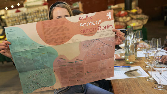 The picture shows a young woman holding a map of Berlin showing all the Austrian Wine Hotspots.