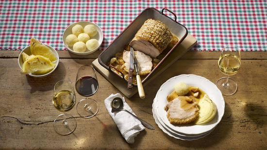 A picture shows roast pork with two white wine and one red wine glass, © AWMB/Blickwerk Fotografie.