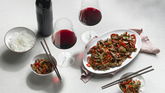The picture shows the dish Sichuan Beef and two glasses of red wine.