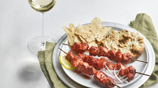 The picture shows the dish tandoori chicken and a glass of white wine.