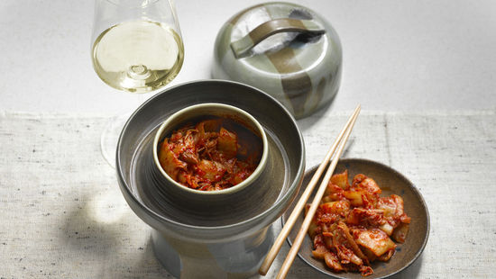 The picture shows the dish kimchi and a glass of white wine.