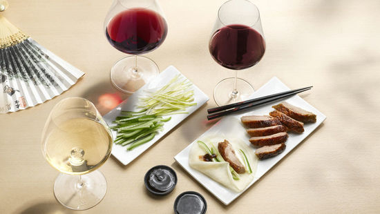 The picture shows a fried peking duck, red wine and white wine.