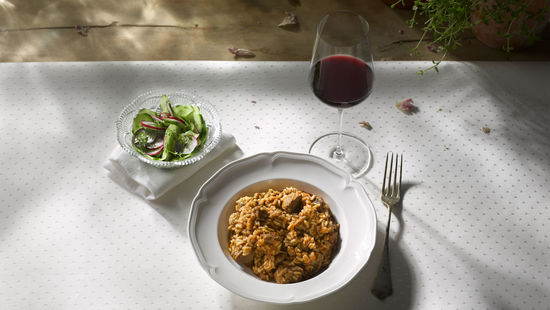 A picture shows a portion of meat rice and a glass of red wine, © Austrian Wine/Blickwerk Fotografie.