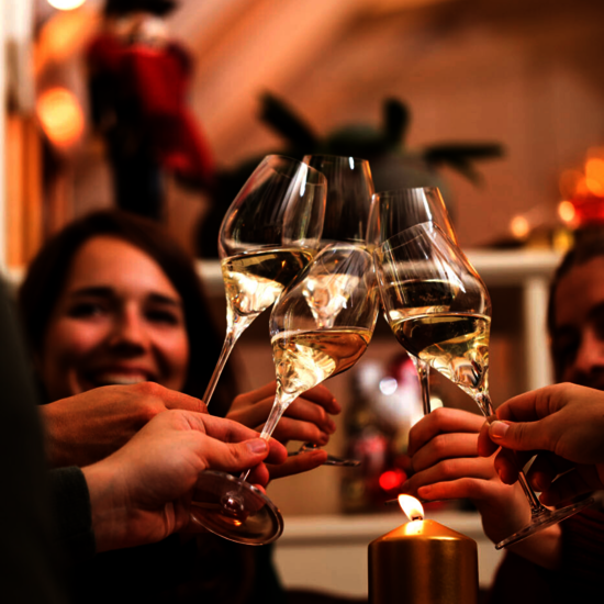 A group of people cheering to each other with a glass of Austrian Sekt