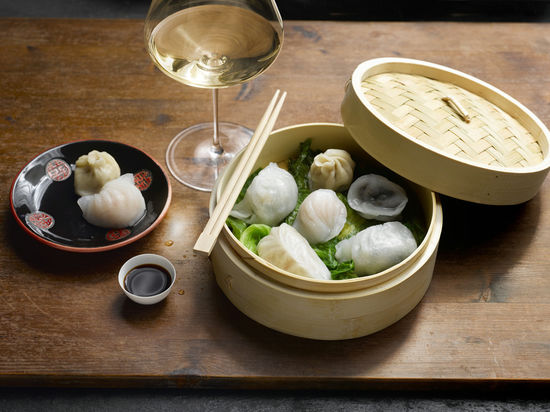 The picture shows Dim Sum on a wooden table and with a glass of white wine.