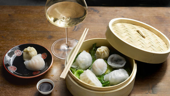 A picture shows a steaming basket with dim sum and a glass of white wine.
