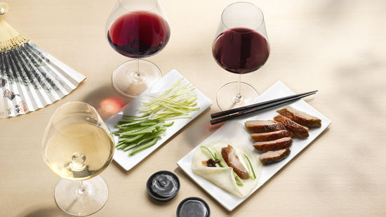 The picture shows the dish peking duck and thre glasses od wine, filled with white wine and red wine,