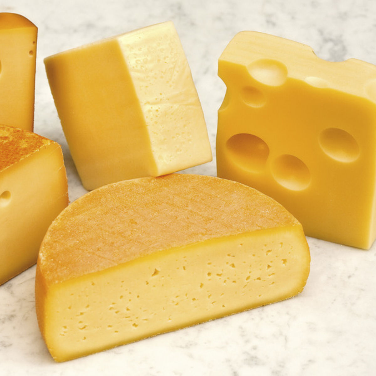 The picture shows several kinds of sliced cheese.