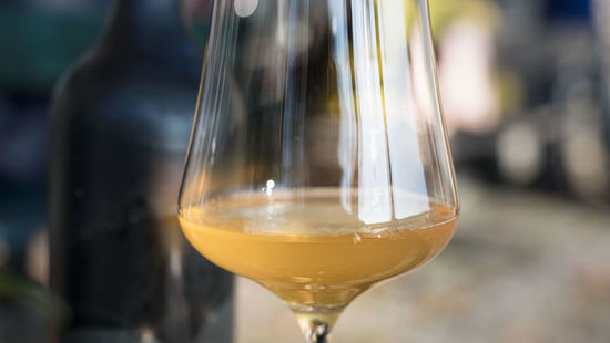 The picture shows a glass of orange wine.