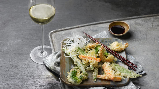 The picture shows the dish tempura and a glass of white wine.